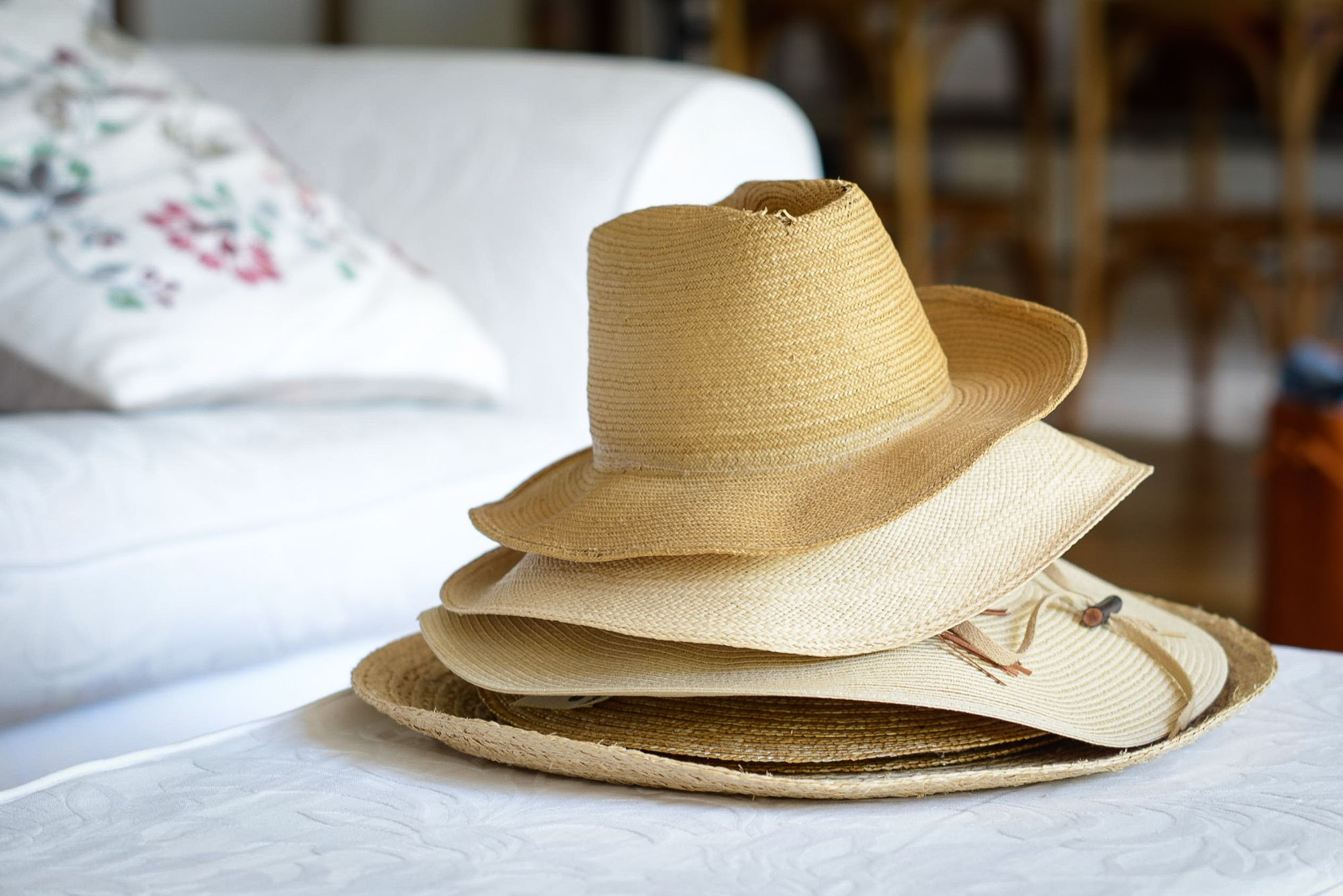 Four summer hats stacked on top of each other